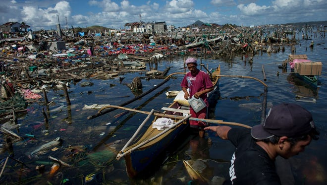 Men load food packages onto boats in Tacloban following Super Typhoon Haiyan on Nov. 18, 2013, in Leyte, Philippines.