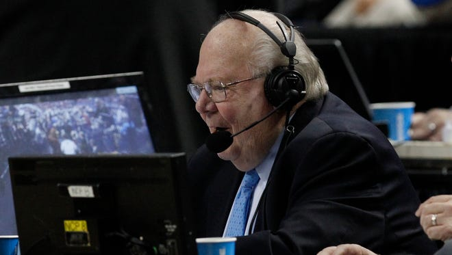 Sportscaster Verne Lundquist works in the second half of a men's college basketball game between Saint Joseph's Hawks and Connecticut Huskies during the 2014 NCAA tournament.