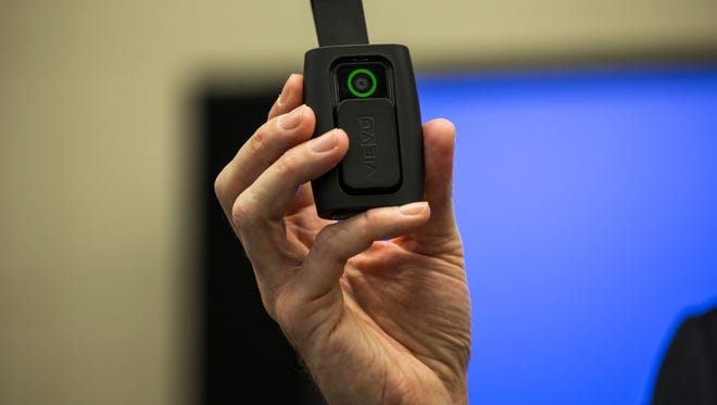 New York City Mayor Bill de Blasio holds a body camera that the police department will begin using.