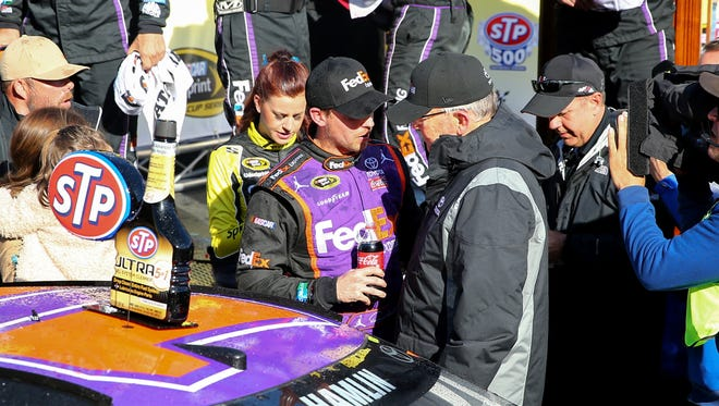 Denny Hamlin, left, is congratulated by car owner Joe Gibbs after winning Sunday's STP 500 at Martinsville Speedway.