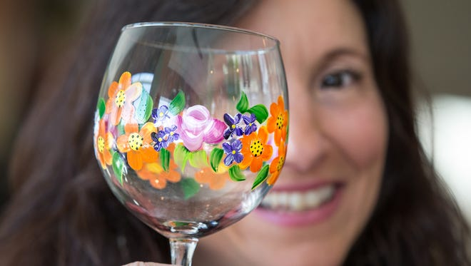 Mary Jean Young shows one of her painted glass items at the Art in the Garden Fine Art Show sponsored by the Altrusa International Club of Oshkosh in 2015.