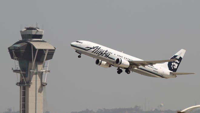 An Alaska Airlines jet passes the air traffic control tower at Los Angles International Airport.
