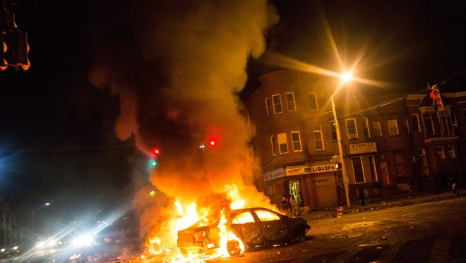 Two cars burn in the middle of an intersection at New Shiloh Baptist Church in Baltimore, Maryland. Riots have erupted in Baltimore following the funeral service for Freddie Gray, who died last week while in Baltimore Police custody.
