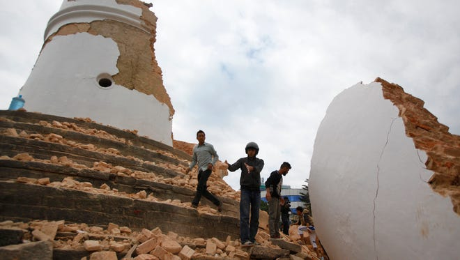 Volunteers work to remove debris at the historic Dharahara Tower after an earthquake in Kathmandu, Nepal, on April 25, 2015.