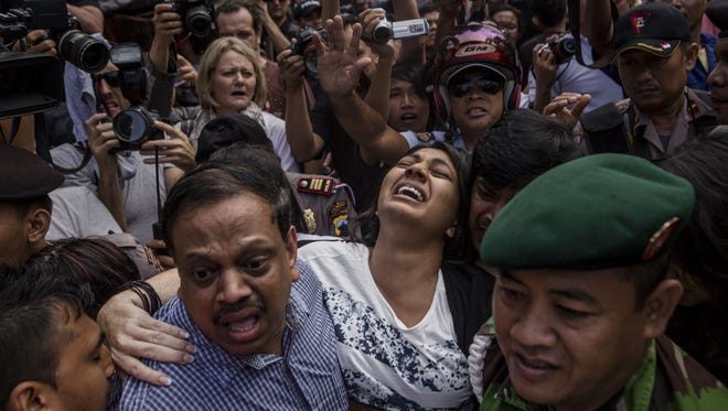 Overcome with grief, Brintha Sukumaran is carried through a crowd of journalists April  28, 2015, as she arrives at Wijaya Pura port for a final visit with her brother, Myuran, before his execution for drug trafficking at Nusakambangan prison in Cilacap, Central Java, Indonesia.