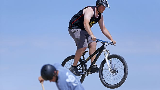 """Mark Shaw rides on the new pump track Saturday, May 2,  2015 in Goodyear, Ariz.  Volunteers worked for five months and donated about 2,500 hours to build what they believe is the West Valley's first """"pump track"""" at Foothills Community Park."""