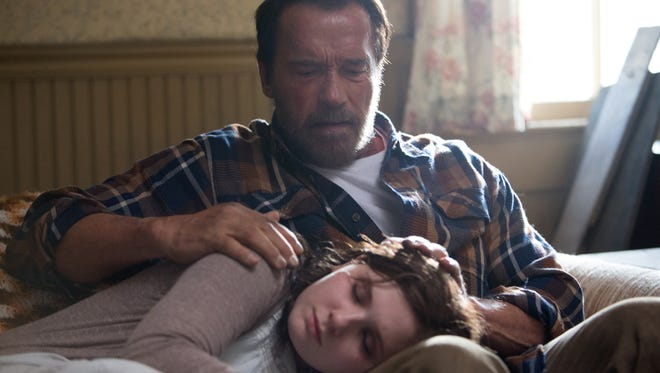 Arnold Schwarzenegger comforts disease-afflicted daughter Abigail Breslin in 'Maggie.'