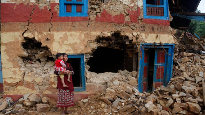 A Nepalese woman stands carrying her child outside her house damaged in last month's earthquake on the outskirts of Lalitpur, Nepal, Monday, May 11, 2015. The April 25 earthquake killed more than 8,000 people and left thousands more homeless, as it flattened mountain villages and destroyed buildings and archaeological sites in the Himalayan region. (AP Photo/Niranjan Shrestha)