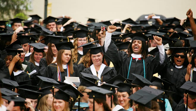 Graduate Ahmed Alkuwaykibi cheers at the end of the Mary Baldwin College commencement ceremony on Sunday, May 17, 2015 as students rise to move their tassles.