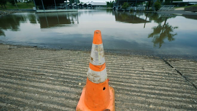 A traffic cone blocks entry to a boat ramp and flooded parking lot at Little Rock Yacht Club Marina near Little Rock, Ark., Friday, May 22, 2015. Downpours have made the Arkansas River unsafe for recreation heading into the Memorial Day weekend, when even more rain is projected to fall across the state