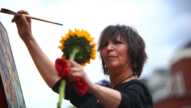 Lorraine Staunch paints a sunflower in front on an audience.