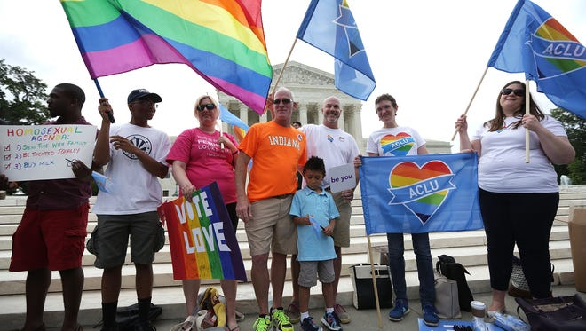 Same-sex marriage supporters hold rainbow flags outside the U.S. Supreme Court June 26, 2015 in Washington, DC. The high court ruled that same-sex couples have the right to marry in all 50 states.