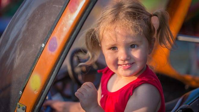 Josslyn Stevens, 2, enjoys a ride in a little helicopter. Oshkosh Sawdust Days 2015 offers a variety of food, entertainment and activities in Menomonie Park