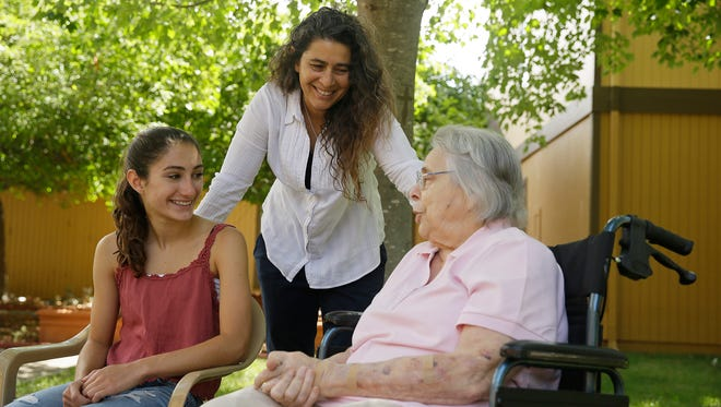 In this photo taken Monday, July 6, 2015, Kamila Al-Najjar, center, visits with her mother, Joan Groen, right, at her assisted living facility as her daughter, Inanna Al-Najjar, 14, left, looks on in Santa Rosa, Calif.  Caught between kids and aging parents, a new poll shows the sandwich generation worries more than most Americans their age about how they'll afford their own care as they grow older. The Utah Department of Health is working to provide better services for individuals with Alzheimer's.