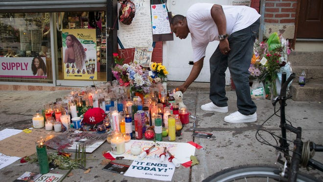 FILE - In this July 22, 2014, file photo, a mourner places a candle at a memorial for Eric Garner, who died while being arrested by New York City police, in Staten Island. Nearly a year has passed since Garner had the encounter with police that led to his death. Since then, his family has become national advocates for police reform and the department is changing how it relates to the public it serves. (AP Photo/John Minchillo. File) ORG XMIT: NYRD202