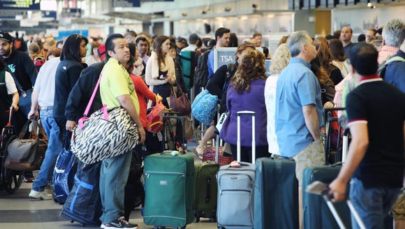 Passengers wait in line at a security checkpoint at