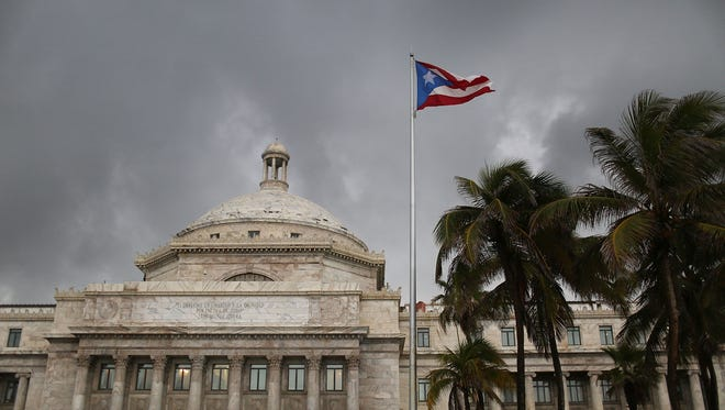 The Puerto Rican flag flies near the Capitol building as the island's residents deal with the government's $72 billion debt.