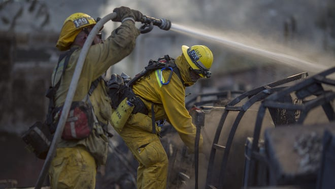 Firefighters hose down the smoldering ruins of a building at the Warm Springs Rehabilitation Center at the Warm Fire on August 16, 2015 in the Angeles National Forest north of Castaic, California. The wildfire has burned six structures and blackened 500 acres so far since it began this afternoon.