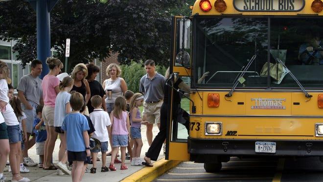 New kindergarten students climb onto a Lakeland school bus at Thomas Jefferson School bus in this file photo.