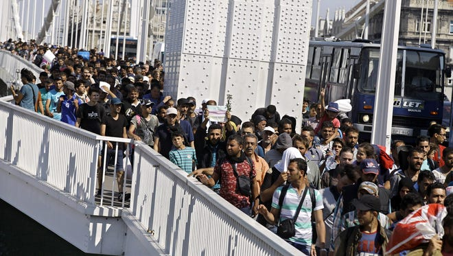 Hundreds of migrants walk across Budapest after leaving the transit zone of the Budapest main train station, on Sept. 4, 2015 intending on walking to the Austrian border.