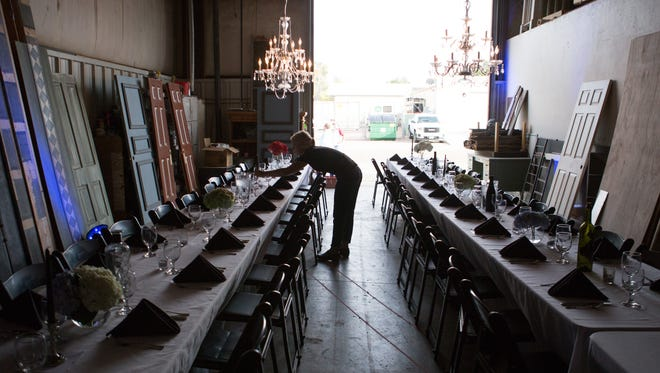 Server Julia Wolkner perfects table settings ahead of the Secret Supper held at Bas Blue Theatre Wednesday, September 30, 2015.