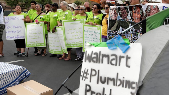 Demonstrators, inlcuding Wal-Mart workers dismissed months ago, protest outside a closed Wal-Mart store in the Los Angeles-area suburb of Pico Rivera, Calif., Thursday, Sept. 10, 2015. The store was one of five around the country closed in the spring. The stores will reopen by November, and the retailer said it is encouraging former workers to reapply for their jobs. But on Thursday, Sept.10, 2015, a complaint was filed with the National Labor Relations Board by the United Food and Commercial Workers International Union, who claim Wal-Mart had no plans to offer jobs to many of its former employees who were actively involved in the fight for higher wages. (AP Photo/Nick Ut)