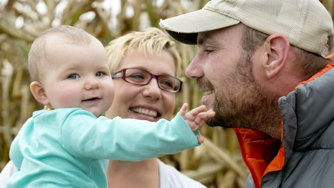 EIght-month-old Audrey Hurda touches her dad, Tim Hurda's face while her mother Holly Hurda holds her in the corn field next to their house in Amherst, Tuesday, Oct. 6, 2015. Tim Hurda is one of two people in Wisconsin to get a recently-approved medical treatment called Duopa to treat his Parkinsons.