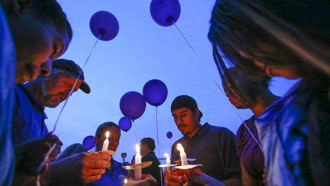 Samantha Grimes, Kraig Lyons, Theresa Lyon, Andres Martinez, Tiffany Robinson pray during a vigil Sunday, Oct. 25, 2015 at Tempe Town Lake in Tempe. The vigil was in honor of Danica Baxter and her children. It was also intended to bring awareness to domestic violence and offer support and solidarity to families affected by it.