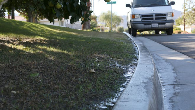 Water flows into the street from misaligned sprinkler heads at a home on Moon Lane in Palm Desert on Oct. 26, 2015.