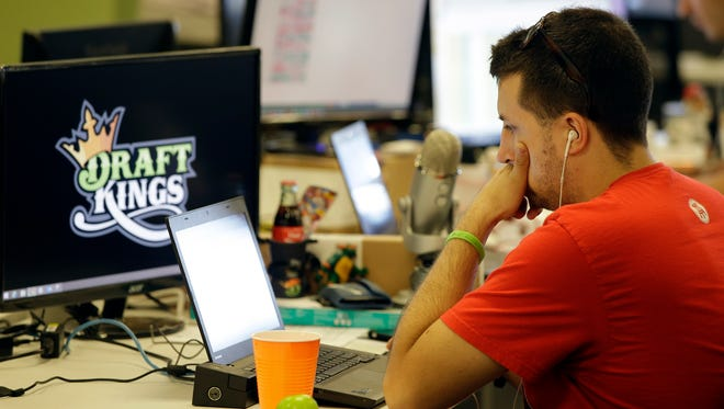 Devlin D'Zmura, a tending news manager at DraftKings, a daily fantasy sports company, works on his laptop at the company's offices in Boston in September