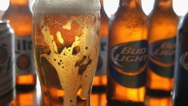 Bottles of Miller Lite and Bud Light beer that are products of SABMiller and Anheuser-Busch InBev (respectively) are shown. The companies agreed to merge.