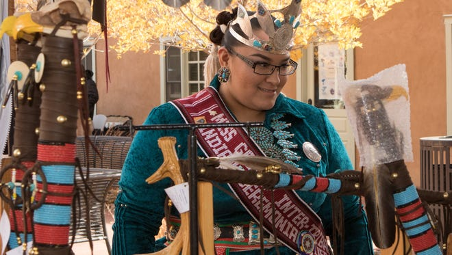 Kahlaya Mckinney of Shiprock, the Gallup Inter-Tribal Indian Ceremonial Queen, peruses the art Saturday during the third annual Native American Market at Mesilla Valley Bosque State Park.