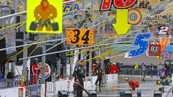 NASCAR pit crews try and dry their stalls as rain falls prior to the 28th Annual Quicken Loans Race for Heroes 500, NASCAR Sprint Cup race Sunday, Nov. 15, 2015 in Avondale, Ariz.