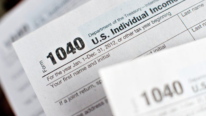U.S. Department of the Treasury Internal Revenue Service (IRS) 1040 Individual Income Tax forms are arranged for a photograph.