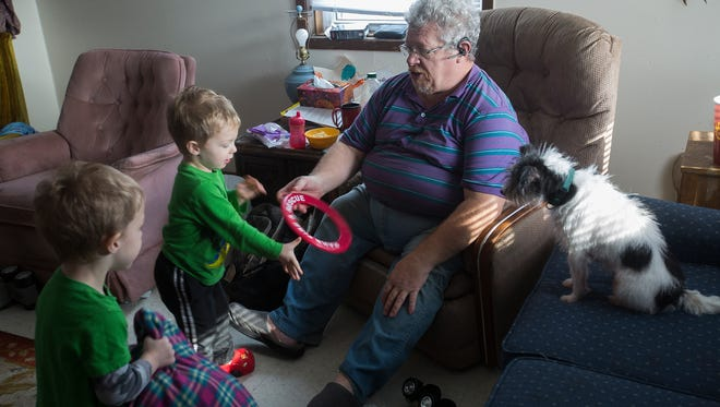 Ron Heginger cares for his twin three-year-old grandsons Johnathan and Princeton Heginger at his apartment in Algona, Wednesday, Nov. 25, 2015. Heginger has been the boys primary caretaker since July 2014. He is currently their power of attorney and is seeking permanent adoption.