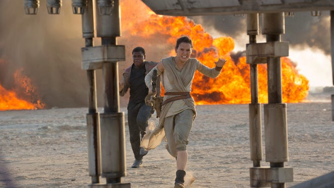 """This photo provided by Disney/Lucasfilm shows Daisy Ridley, right, as Rey, and John Boyega as Finn, in a scene from the film, """"Star Wars: The Force Awakens,"""" directed by J.J. Abrams."""