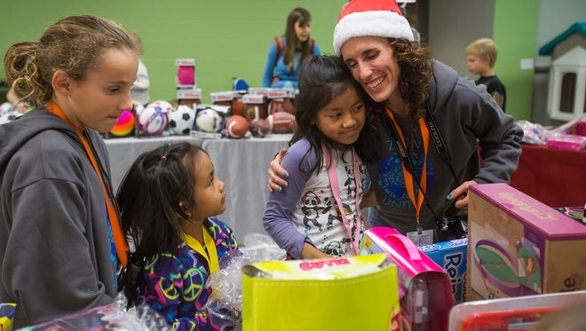 Sherilyn Rittgers of Ankeny, right, hugs Laura Thangi, 9, while Rittgers's daughter Emma, 12, left, helps Thangi's little sister Hanna, 5, shops for toys at Zion Evangelical Lutheran Church in Des Moines, Wednesday, Dec. 16, 2015. The Thangi sisters moved to Des Moines after living in a refugee camp in Malaysia. The church gave away presents to 600 children.