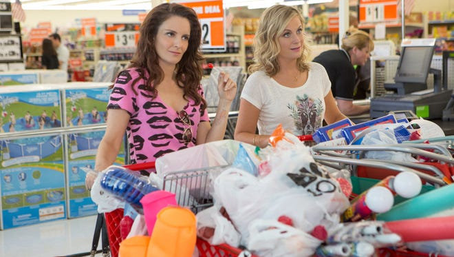 "This photo provided by Universal Pictures shows, Tina Fey, left, as Kate Ellis and Amy Poehler as Maura Ellis, in a scene from the film, ""Sisters,"" directed by Jason Moore. (K.C. Bailey/Universal Pictures via AP)"