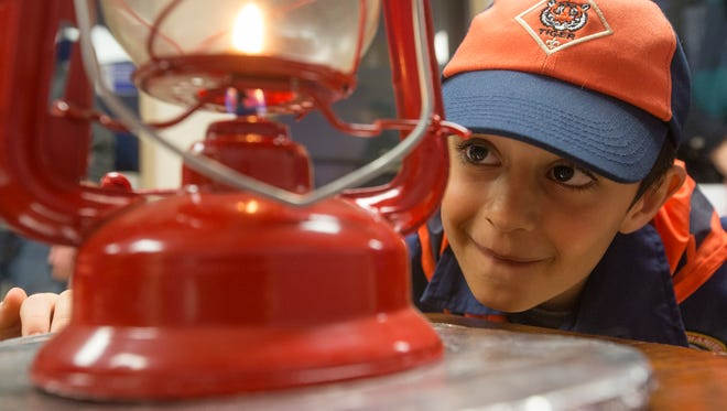 "Cub Scout Ayian Khan, 7, helps ""spread the flame"" at Iowa Religious Media Services in Urbandale, Thursday, Dec. 17, 2015. The flame originated in a grotto in Bethlehem close to the site where historians believe Jesus Christ was born."