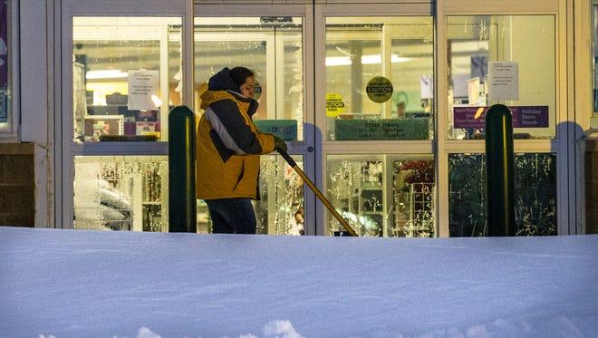A store employee shovels snow that drifted near the door Tuesday, Dec. 29, 2015, at Shopko, 1300 S. Koeller St., Oshkosh.