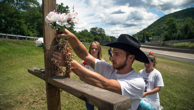 Adam Moorehead attaches flowers to a memorial for his brother Robert Moorehead III, who was killed by a drunk driver and would have turned 30 years old on August 5, 2015.