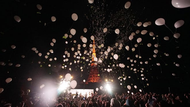 Peoples release balloons to celebrate the New Year with Tokyo Tower in the background  in Tokyo, early Friday, Jan. 1, 2016. Japan celebrated the start of 2016, the Year of the Monkey in the Japanese Zodiac.