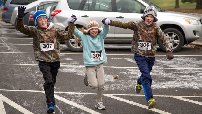 Isaac Clark, 13, Tessa Clark, 10, and Aiden Clark 13, all of Alachua, Florida, hold hands moments before crossing the finish line of the Freeze 10k held by Triple City Runners Club in Ostiningo Park on Saturday, January 2, 2016. The three siblings were in town visiting their great grandma and decided to run the race with their father.