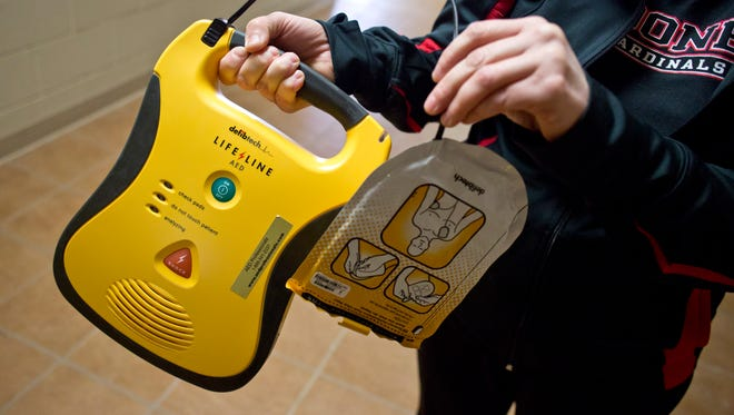 Athletic Director Kelly Loria shows an AED device located in a first floor hallway of the main building Tuesday, Jan. 5, 2016 at Cardinal Mooney High School in Marine City. Senate Bill 647 would require that public and private middle and high schools provide instruction and certification in CPR and the use of an AED device.