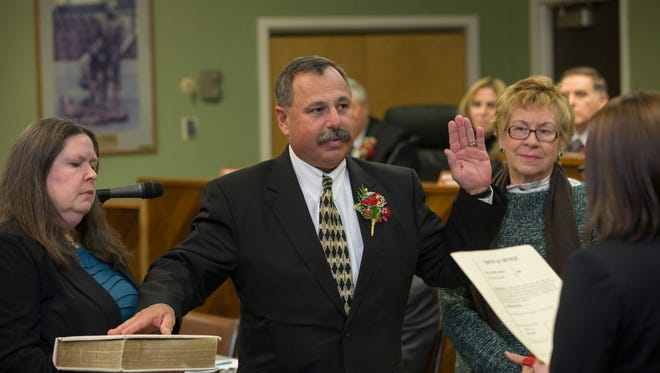 Barnegat Mayor John J. Novak is sworn in with wife Jenny holding the Bible and his mother Marie McGill looking on.