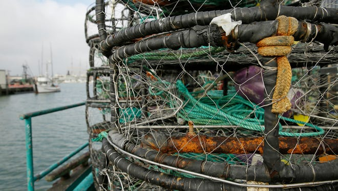 Crab pots are stacked along a fish processing pier.