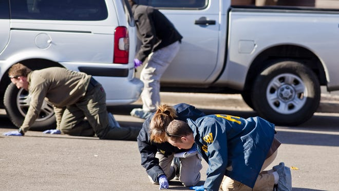 FBI agents and Tucson-area law enforcement officers scour the parking lot of the Safeway at Oracle and Ina Roads near Tucson looking for evidence Monday two days after a mass shooting at the Safeway where U.S. Rep. Gabrielle Giffords was shot.