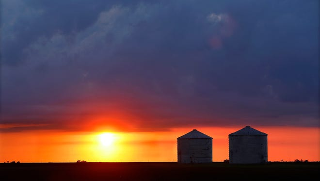 Storm clouds form over central Illinois corn and soybean grain bins Tuesday, May 21, 2013, in Pleasant Plains, Ill. (AP Photo/Seth Perlman)