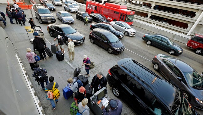 Holiday travelers appear at Los Angeles International Airport, on Tuesday, Nov. 24, 2015. An estimated 46.9 million Americans are expected to take a car, plane, bus or train at least 50 miles from home over the long holiday weekend, according to the motoring organization AAA. (AP Photo/Nick Ut) ORG XMIT: LA102