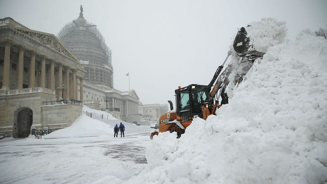 A bulldozer clears snow on the East Front of the U.S. Capitol on Saturday,  in Washington, D.C.